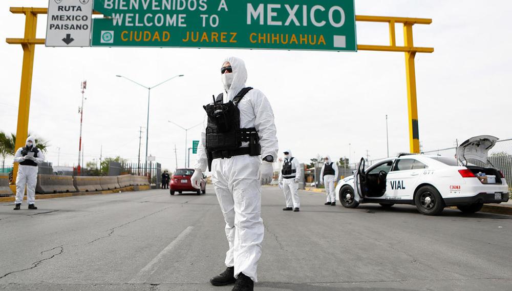 Miembros de la Policía del Estado de Chihuahua, vestidos con trajes protectores, participan en una campaña de información y prevención contra la pandemia de coronavirus -COVID-19-, en el Puente Internacional Córdoba-De las Américas en Ciudad Juárez, Chihuahua, México, el 29 de marzo de 2020. HERIKA MARTINEZ AFP