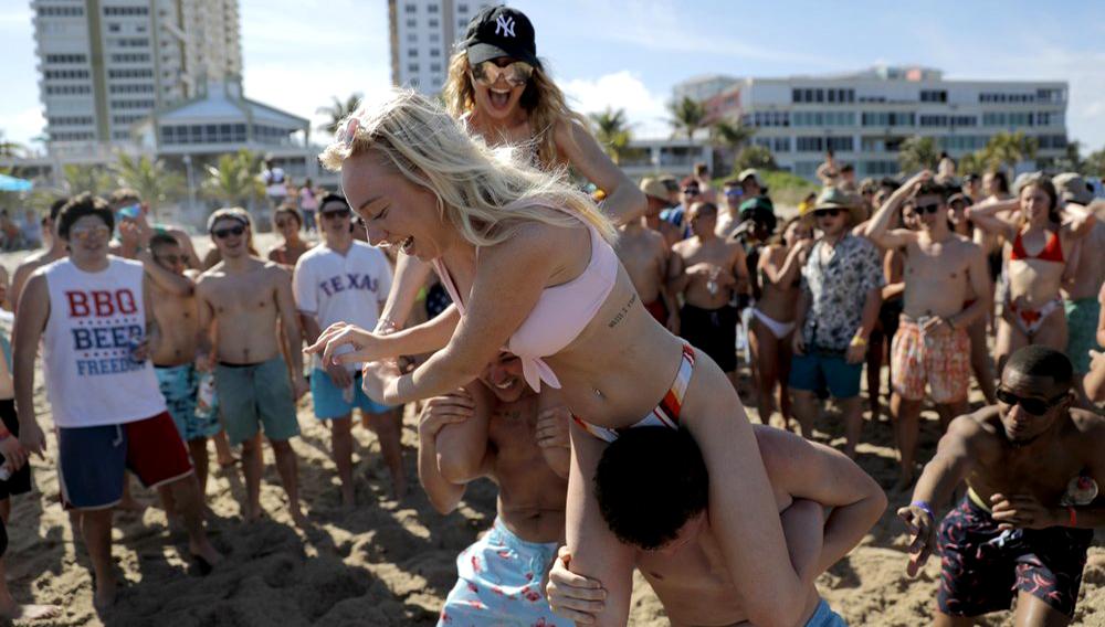 Cece Guida, de 19 años y procedente de la ciudad de Nueva York, sobre Sam Reddick, de 20 años y procedente de Evansville, Indiana, durante un juego organizado durante las vacaciones de primavera en una playa el 17 de marzo de 2020 en Pompano Beach, Florida. (AP Foto/Julio Cortez)
