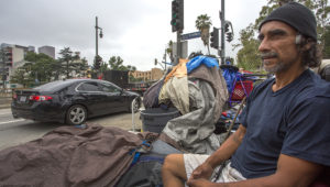 LOS ANGELES, CA - JUNE 01: Cars pass the encampment of a man whose been homeless for about two years on May 1, 2017 in Los Angeles, California. (Photo by David McNew/Getty Images)