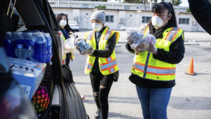 LAUSD employees Kimberly Alegria, Marcela Navarrete and Citlali Nava bring meals to the back of a vehicle at the LAUSD 'grab and go' center at Van Nuys High School on Wednesday, March 18, 2020. (Photo by Sarah Reingewirtz, Pasadena Star-News/SCNG)