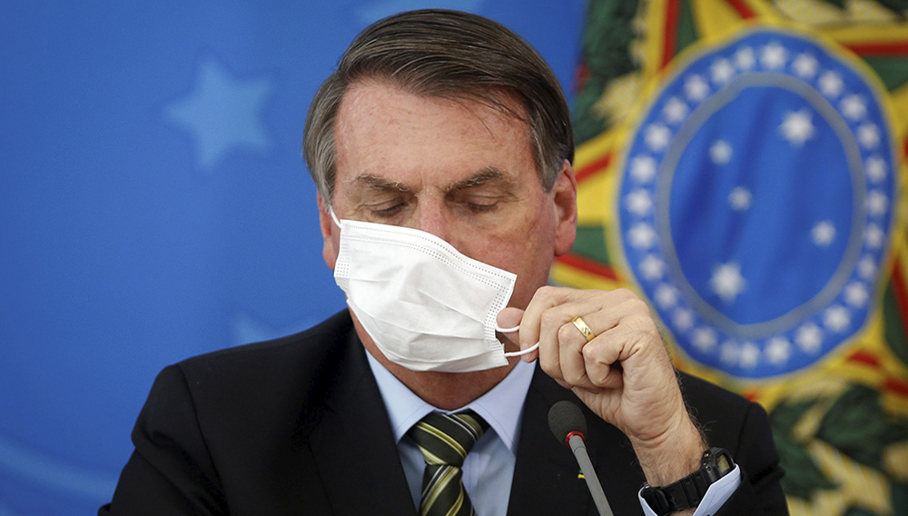 Brazil's President Jair Bolsonaro adjusts his protective face mask during a press statement to announce federal judiciary measures to curb the spread of the coronavirus disease (COVID-19) in Brasilia, Brazil March 18, 2020. Picture taken March 18, 2020. REUTERS/Adriano Machado (UESLEI MARCELINO/)