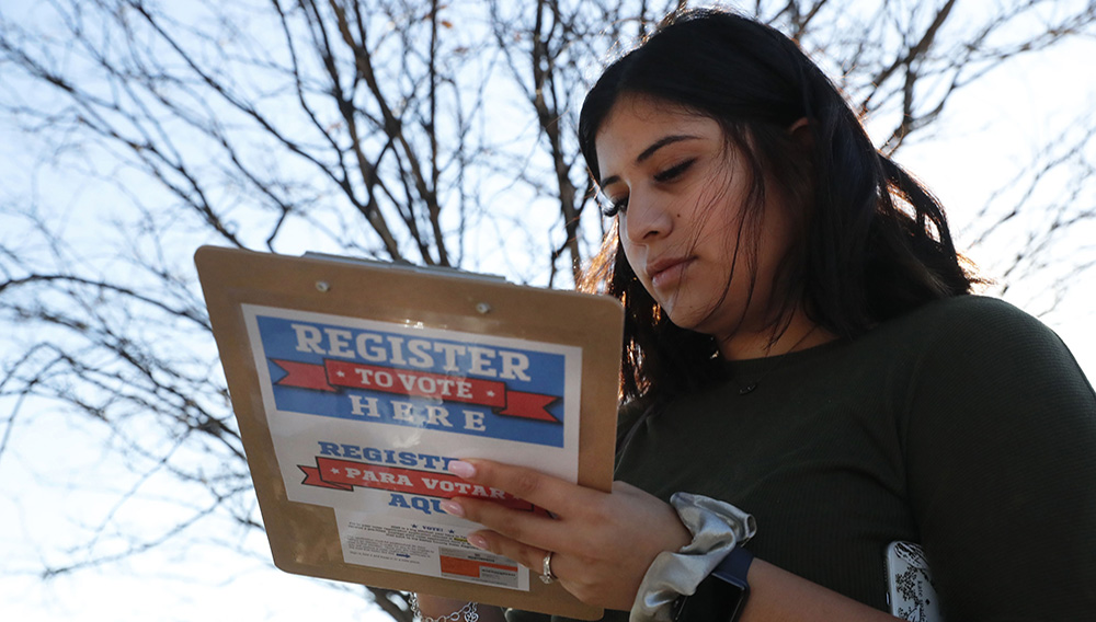 Karina Shumate, 21, a college student studying stenography, fills out a voter registration form in Richardson, Texas, Saturday, Jan. 18, 2020. Democrats are hoping this is the year they can finally make political headway in Texas and have set their sights on trying to win a majority in one house of the state Legislature. (AP Photo/LM Otero)