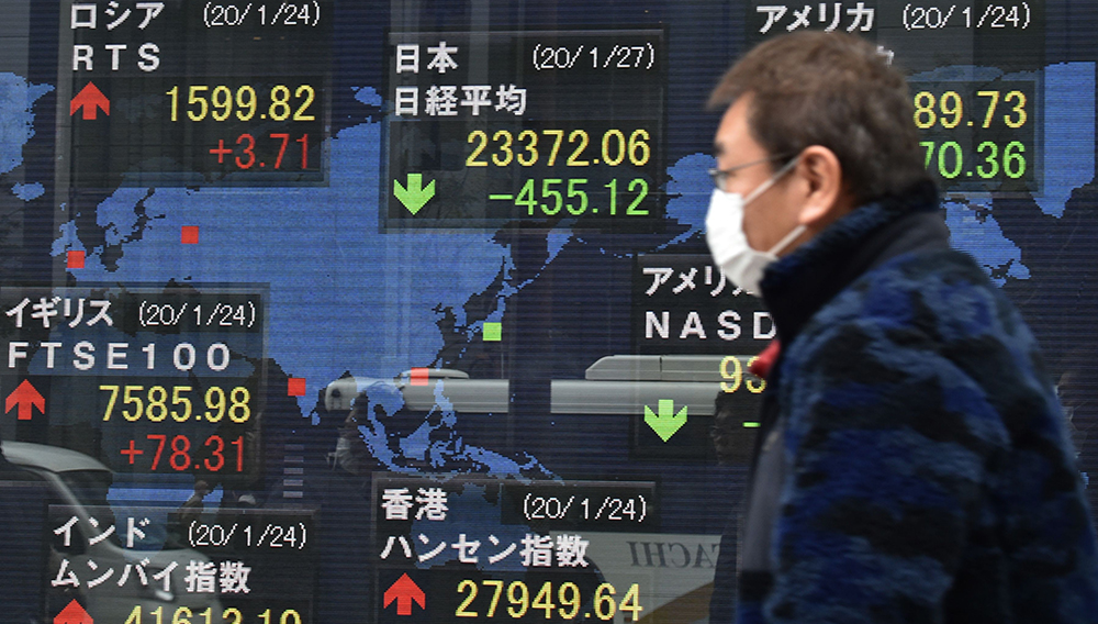 A pedestrian walks in front of an electric quotation board displaying share prices of world bourses, including the Tokyo Stock Exchange (top C), along a street in Tokyo on January 27, 2020. KAZUHIRO NOGI | AFP via Getty Images