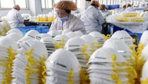This photo taken on February 28, 2020 shows workers producing face masks at a factory in Handan in China's northern Hebei province. - The number of deaths globally in the new coronavirus outbreak passed 3,000 on March 2, as China reported more 42 deaths. (Photo by STR / AFP) / China OUT