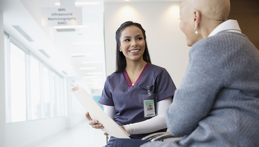 Female nurse discussing medical chart with bald cancer patient in waiting room. Shutterstock