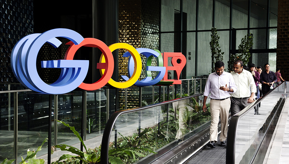 People ride a moving walkway in front of a sign featuring Google Inc.'s logo at the company's Asia-Pacific headquarters during its opening day in Singapore, on Thursday, Nov. 10, 2016. ORE HUIYING—BLOOMBERG VIA GETTY IMAGES