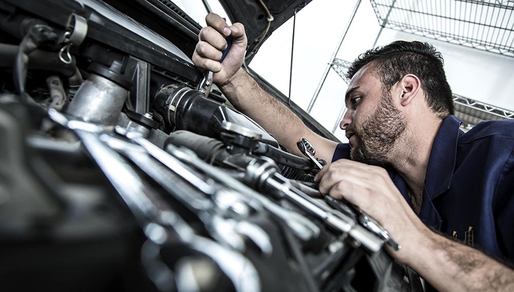 Mecánico de autos fijando un motor en un garaje. FOTO: Jcfotografo | Dreamstime.com