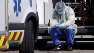 A health worker wearing a protective gear takes a break during transfer operations of patients infected with coronavirus disease (COVID-19) from Strasbourg to Germany and Switzerland, France March 30, 2020. REUTERS/Christian Hartmann
