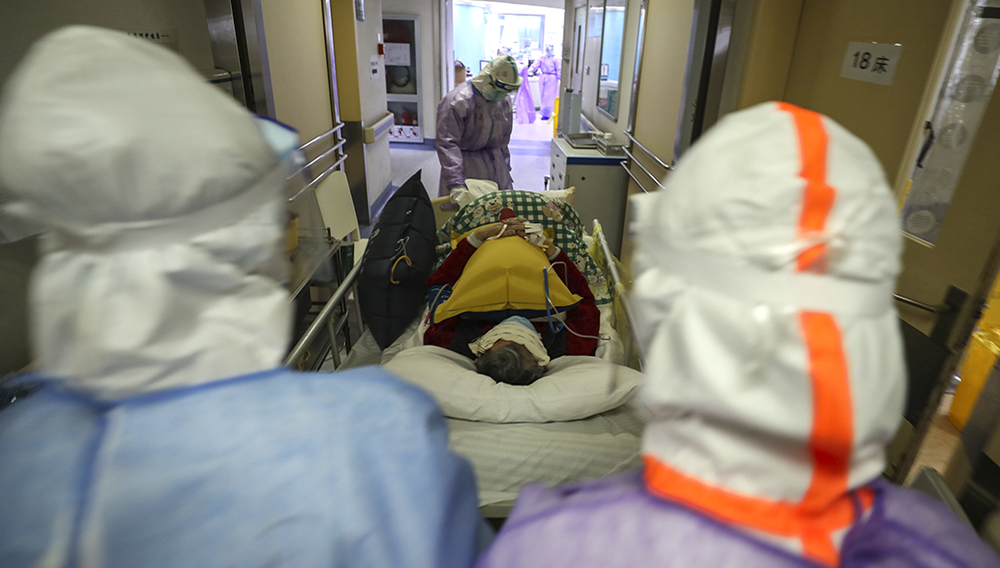 This photo taken on February 28, 2020 shows medical staff transferring a patient infected by the COVID-19 coronavirus at the Red Cross hospital in Wuhan in China's central Hubei province. - China on March 1 reported 35 more deaths from the new coronavirus, taking the toll in the country to 2,870. (Photo by STR / AFP) / China OUT