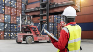 Foreman control loading containers box from cargo freight ship. | Weerasak Saeku/Shutterstock