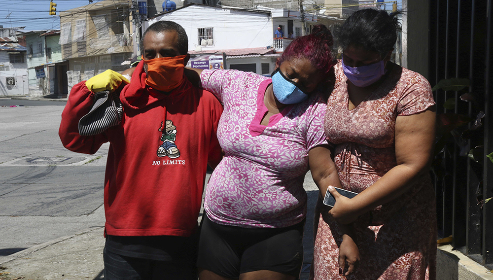 Mariela Jacome, right, helps to her mother Catherine Quinonez, center, suffering of COVID-19, arrive to Hospital del día Jacobo & Maria Ratinoff in Guayaquil, Ecuador, Thursday, 16, 2020. (AP Photo/Angel de Jesus)