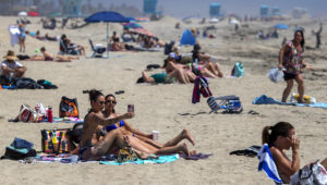 Cailin Healy, and an unidentified friend, both of Calabasas, take a selfie together as beach-goers enjoy warm summer-like weather amid state and city social distancing regulations mandated by Gov. Newsom in Huntinton Beach, CA, on April 22, 2020. Allen J. Schaben | Los Angeles Times via Getty Images