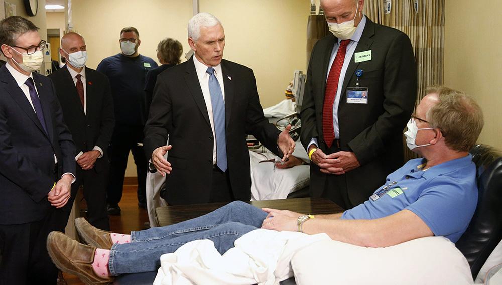 El vicepresidente de Estados Unidos, Mike Pence (centro), visita a Dennis Nelson, un paciente que sobrevivió al coronavirus y se dispone a donar sangre, durante una visita a la Clínica Mayo, el 28 de abril de 2020, en Rochester, Minnesota, donde recorrió las instalaciones en apoyo a la investigación y tratamiento del COVID-19. (AP Foto/Jim Mone)