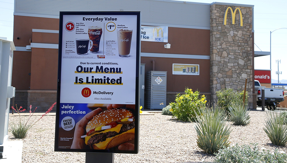In this April 20, 2020 file photo, a new sign lets drive-thru customers know that the available menu at a local McDonalds is no longer complete due to the ongoing coronavirus restrictions in Phoenix. (AP Photo/Ross D. Franklin)