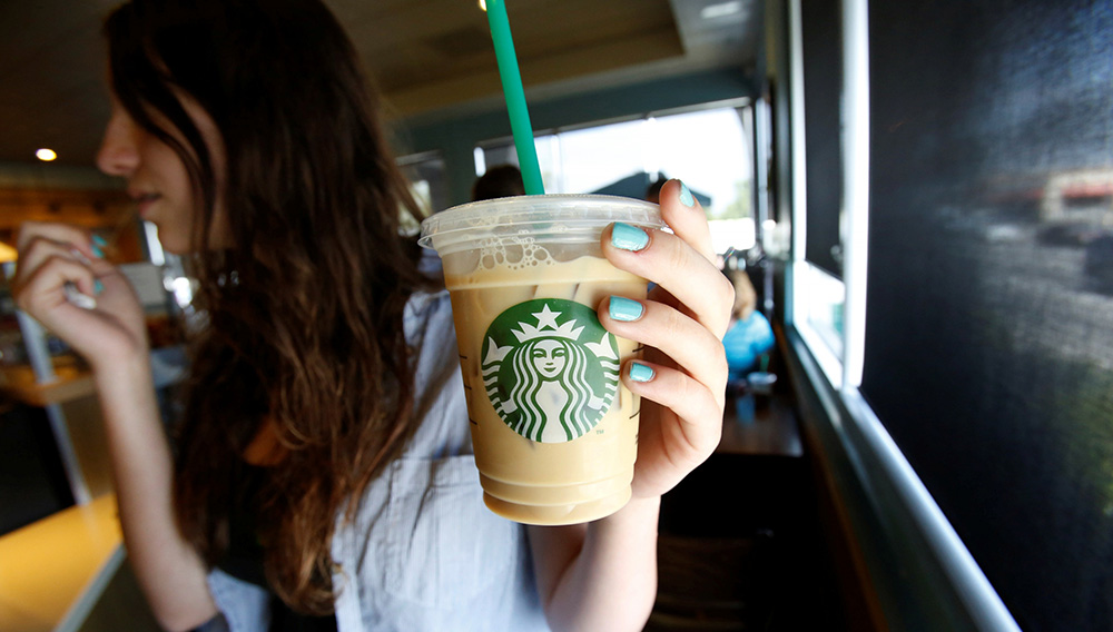 A patron holds an iced beverage at a Starbucks coffee store in Pasadena, Calif., July 25, 2013. | Reuters