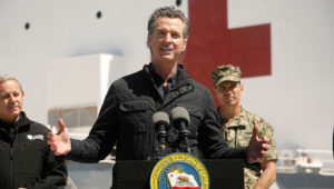 California Gov. Gavin Newsom, flanked by Director Mark Ghilarducci, Cal OES, and Admiral John Gumbleton, United States Navy, speaks in front of the hospital ship USNS Mercy after it arrived into the Port of Los Angeles on March 27, 2020. (CAROLYN COLE/POOL/AFP via Getty Images)