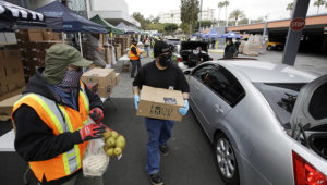Volunteers load up vehicles at a food distribution center April 17, 2020, in the Crenshaw district of Los Angeles. As the coronavirus drives unemployment, food banks have seen a spike. | Associated Press