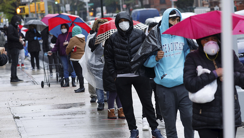 People wear protective face masks on Friday as they wait in line to receive free food at a curbside pantry for needy residents in Brooklyn. (Mike Segar/Reuters)