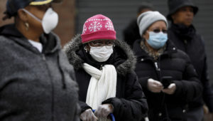People wearing protective masks wait in line for donated food distribution at the Queensbridge Houses on April 21, 2020. | REUTERS/Andrew Kelly/File Photo