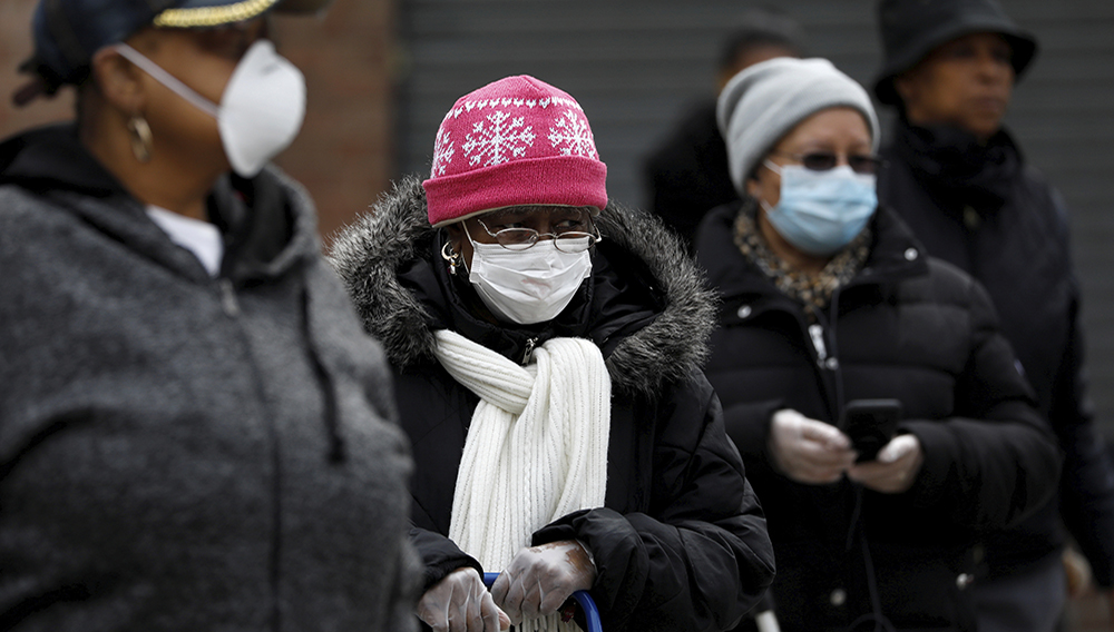 People wearing protective masks wait in line for donated food distribution at the Queensbridge Houses on April 21, 2020.   REUTERS/Andrew Kelly/File Photo