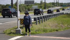A woman wears a mask as she waits for the motorcade for President Donald Trump to go past, Saturday, May 23, 2020, in Sterling, Va. Trump is en route to Trump National Golf Club. (AP Photo/Alex Brandon)