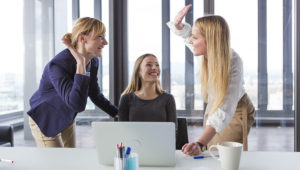 Three business women in modern office celebrating good project results. | Photo: Shutterstock