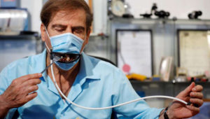 Meir Gitelis, co-developer of an Israeli company, eats while wearing a mask fitted with a mechanical mouth that opens to enable diners to eat without taking it off, as the coronavirus disease (COVID-19) restrictions ease, at Avtipus Patents and Inventions lab in Or Yehuda, Israel May 18, 2020. REUTERS/Amir Cohen