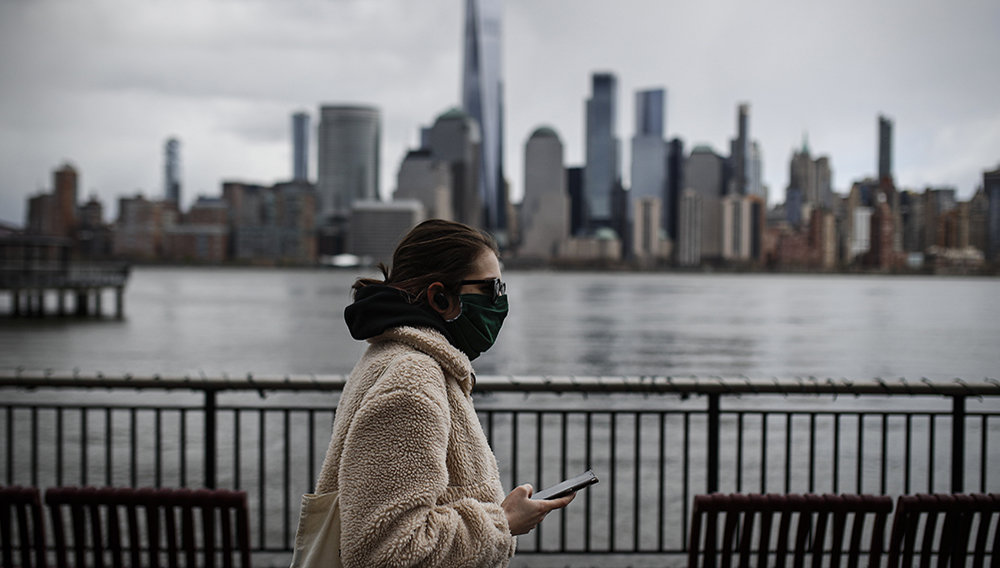 FILE- In this April 10, 2020 file photo a woman wearing a face mask sure to CVID-19 concerns walks along the Jersey City waterfront with the New York City skyline in the background. (AP Photo/John Minchillo File)