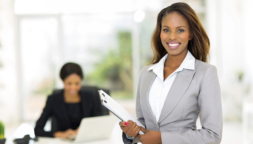 Beautiful african businesswoman holding clipboard.   PHOTO: Michael Zhang - Delight Images