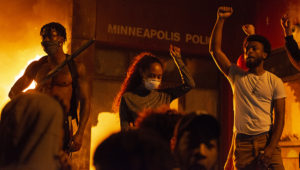 Protesters raise a fist in front of the burning Minneapolis 3rd police precinct on Thursday, May 28, 2020, during the third day of protests over the death of George Floyd in Minneapolis. | Anadolu Agency