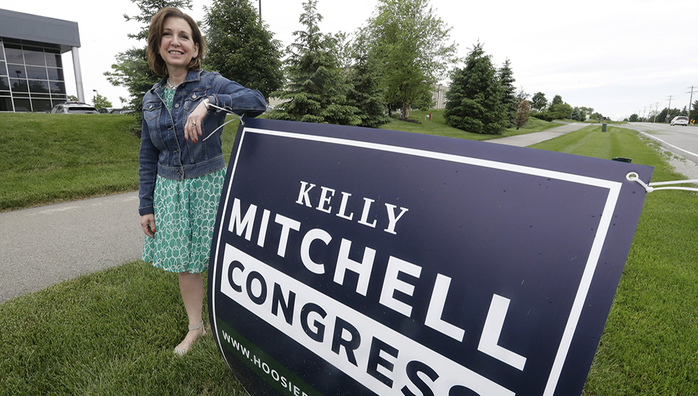 Indiana State Treasurer Kelly Mitchell stands by a campaign sign, Thursday, May 28, 2020, in Westfield, Ind. Mitchell is a candidate for Indiana's 5th Congressional District. (AP Photo/Darron Cummings)