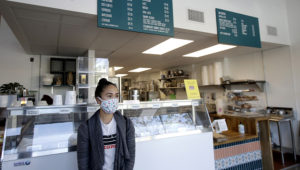 Rica Sunga-Kwan, owner of Churn Urban Creamery, wears a mask while interviewed at the shop in San Francisco, Thursday, April 23, 2020. Churn, which had closed days before San Francisco's shelter in place orders for coronavirus concerns, reopened on April 1, for online orders and curbside pickup, and created an online store to sell supplies such as flour, sugar, toilet paper and other items they had for their ice cream business to customers. (AP Photo/Jeff Chiu)