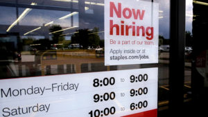 """A """"Now hiring"""" sign is displayed on the front door of a Staples store in Manchester, N.H., on Aug. 15, 2019. (Associated Press)"""
