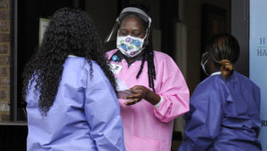 """In this May 27, 2020, photo, health care workers talk outside a Lowndes County coronavirus testing site in Hayneville, Ala. Experts say Lowndes County and nearby poor, mostly black counties in rural Alabama are now facing a """"perfect storm"""" as infections tick up: a lack of access to medical care combined with poverty and the attendant health problems that can worsen the outcomes for those who become sick. (AP Photo/Jay Reeves)"""