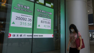 A woman wearing a face mask walks past a bank electronic board showing the Hong Kong share index at Hong Kong Stock Exchange Tuesday, June 9, 2020. Asian shares were mixed on Tuesday after the Nasdaq hit a record high. (AP Photo/Vincent Yu)
