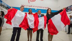 Ciudadanos de nacionalidad peruana con la bandera del país. Foto: Superintendencia Nacional de Migraciones.