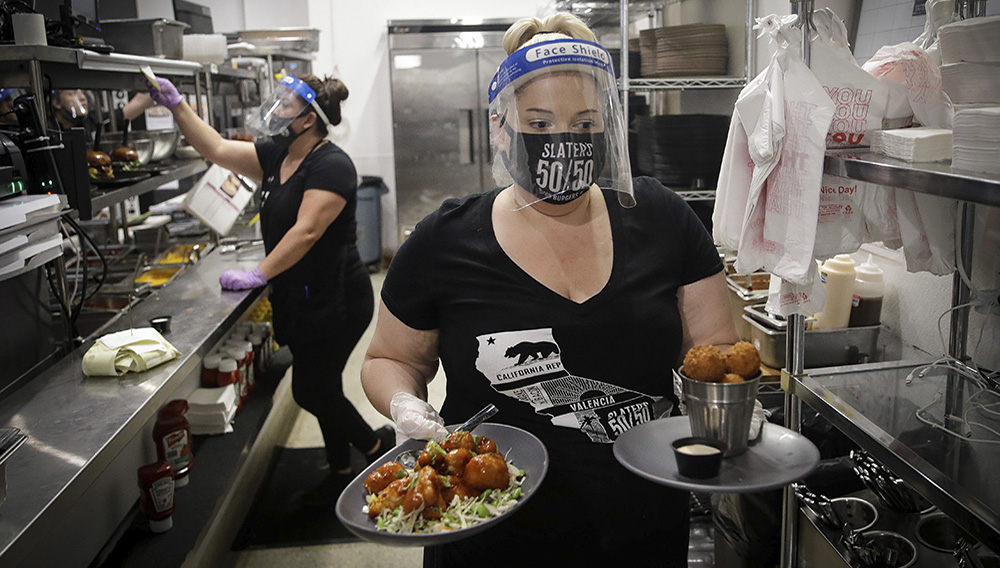 A waitress takes a food order from the kitchen at Slater's 50/50 Wednesday, July 1, 2020, in Santa Clarita, California. (AP Photo/Marcio Jose Sanchez)