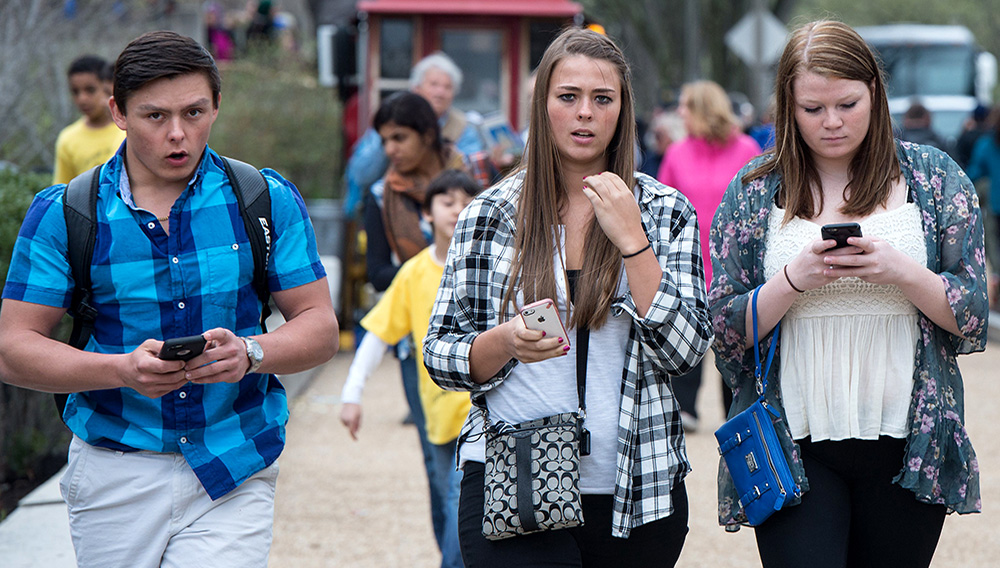 Three teens walk with their smartphones as they walk outside the Natural History Museum in Washington on April 8, 2015. CREDIT: Nicholas Kamm/AFP/Getty Images