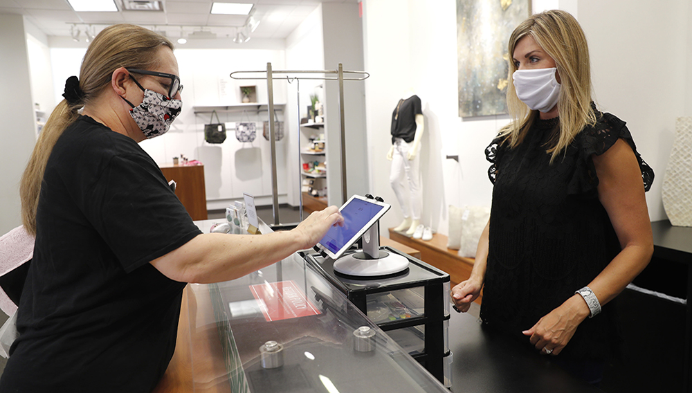 FILE In this Wednesday, May 13, 2020 FILE photo, Monique Kursar, left, completes a purchase with Amy Witt, owner of the Velvet Window, in Dallas. (AP Photo/LM Otero)