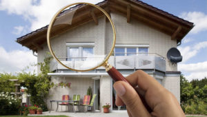 Person's Hand Holding Magnifying Glass Over Luxury House. | Photo: Dreamstime