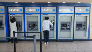 FILE - In this March 24, 2020 file photo, a Chase bank employee, right, disinfects the branches ATMs to fend off coronavirus as a customer uses another in the Flushing neighborhood of the Queens borough of New York. (AP Photo/Mary Altaffer, File)
