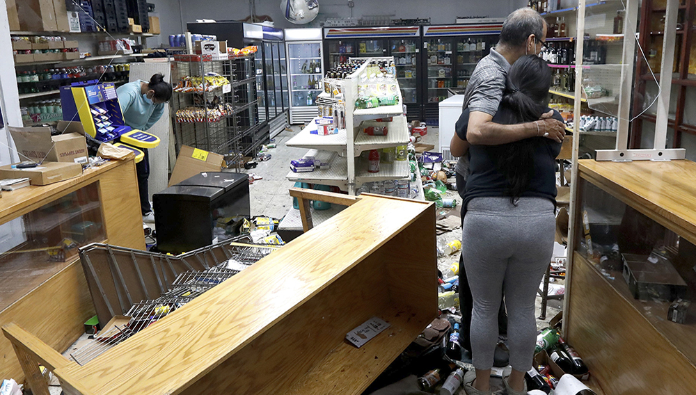Yogi Dalal hugs his daughter Jigisha as his other daughter Kajal, left, bows her head at the family food and liquor store Monday, Aug. 10, 2020, after the family business was vandalized in Chicago. | Charles Rex Arbogast, AP
