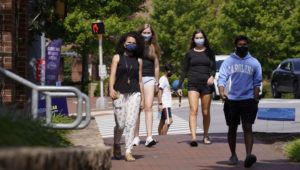 FILE - In this Aug. 18, 2020, file photo, students wear masks on campus at the University of North Carolina in Chapel Hill, N.C. As more and more schools and businesses around the country get the OK to reopen, some college towns are moving in the opposite direction because of too much partying and too many COVID-19 infections among students. (AP Photo/Gerry Broome, File)
