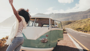 Woman on roadtrip standing outdoors on countryside road near a mini van. Female having fun on vacation. | Jacob Lund/Shutterstock