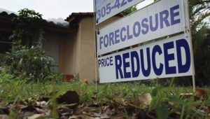 A foreclosure/price reduced sign stands in front of a home for sale on February 11, 2011 in Miami, Florida. | JOE RAEDLE—GETTY IMAGES