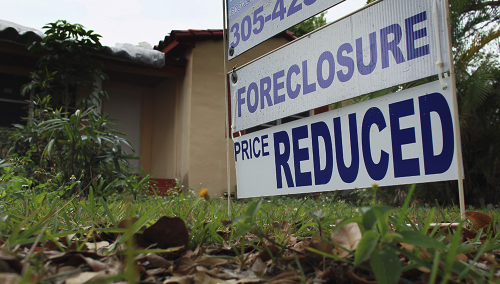 A foreclosure/price reduced sign stands in front of a home for sale on February 11, 2011 in Miami, Florida.   JOE RAEDLE—GETTY IMAGES