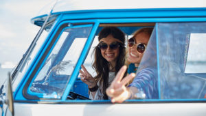 Smiling young hippie women driving minivan car. | Photo: Syda_Productions / Depositphotos