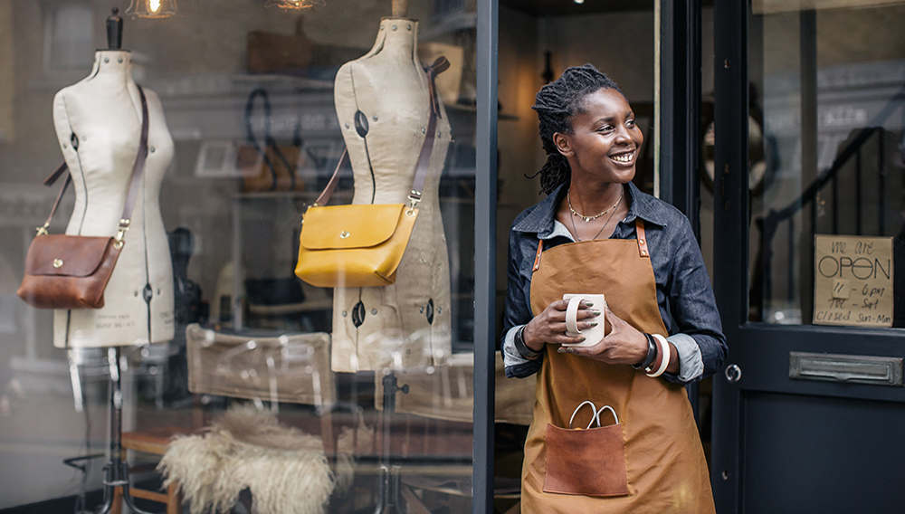 A small business owner stands outside her handbag shop. | Photo: Getty Images