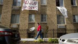 """In this May 20, 2020 file photo, signs that read """"No Job No Rent"""" hang from the windows of an apartment building in Northwest Washington. ANDREW HARNIK — AP PHOTO"""