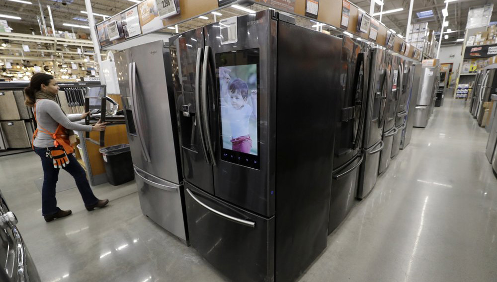 In this Jan. 27, 2020 file photo a worker pushes a cart past refrigerators at a Home Depot store location in Boston. On Thursday, June 25, orders to American factories for big-ticket goods rebounded last month from a disastrous May as the U.S. economy began to slowly reopen. (AP Photo/Steven Senne)